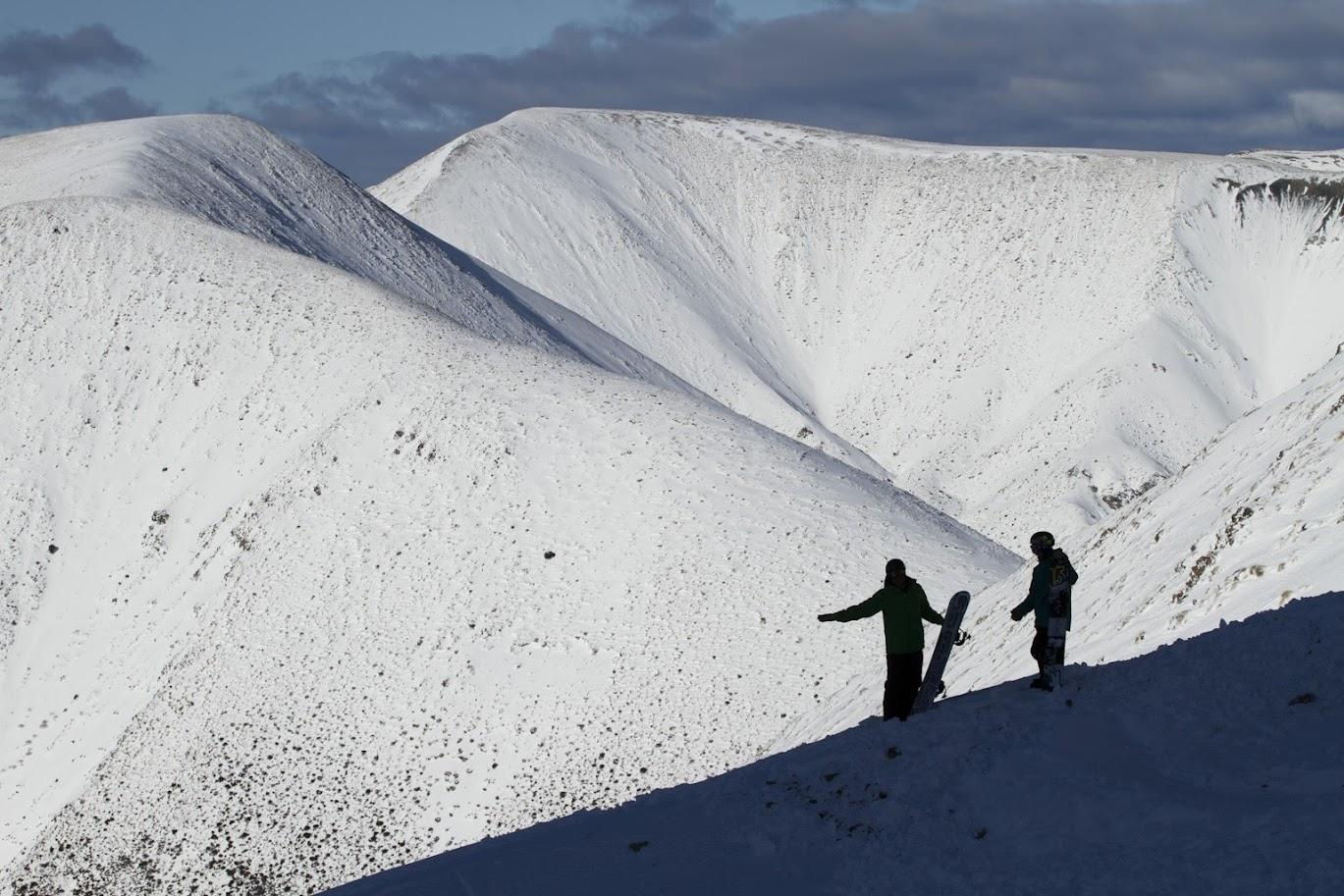 snowboarders on a mountain ridgeline