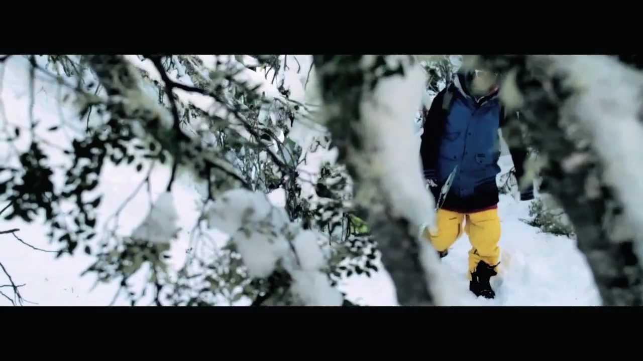 snowboarder walking through the forrest