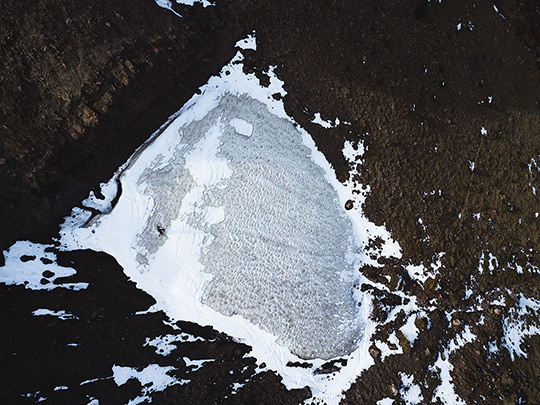 drone photo of a snowboarder on a small patch of snow