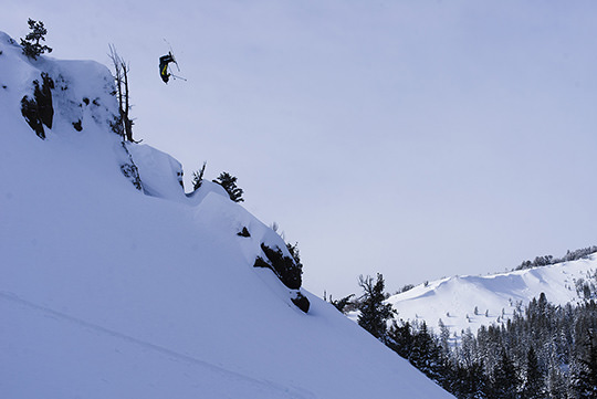 skier backflipping off a cliff into fresh powder