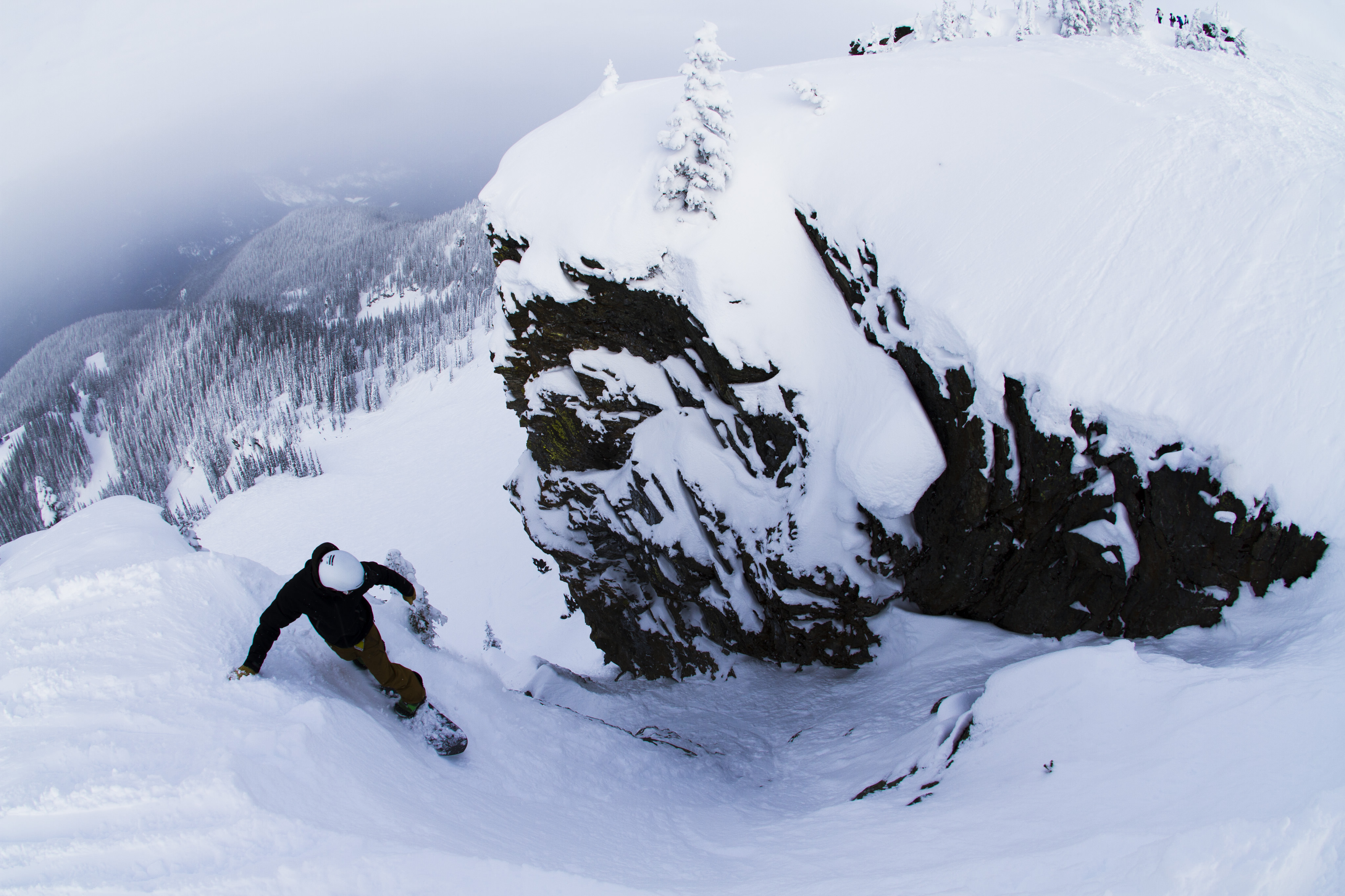 snowboarder dropping into a rocky chute